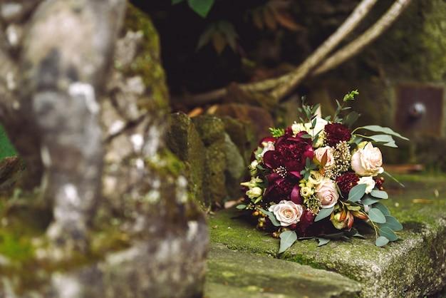 Il ricco bouquet da sposa rosso autunnale giace sulle orme di pietra