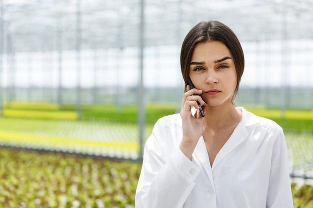 Il ricercatore parla al telefono camminando intorno a una serra