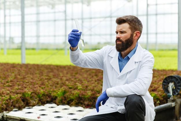 Il ricercatore prende l'acqua in una provetta seduta in una serra