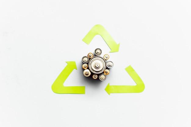 Il riciclaggio dei rifiuti, lo smaltimento dei rifiuti, l'ambiente e il concetto di ecologia - close up di batterie alcaline usate e simbolo di riciclaggio verde
