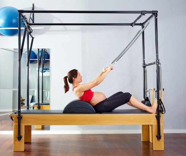 Il riformatore dei pilates della donna incinta rotola sull'esercizio