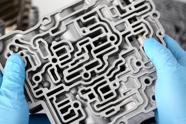 Il riparatore del servizio di riparazione automatica in cambi automatici tiene in mano in guanti protettivi blu il dettaglio del hydroblock disidrata la diagnostica e il primo piano di trasmissione del test di stima dei dettagli.