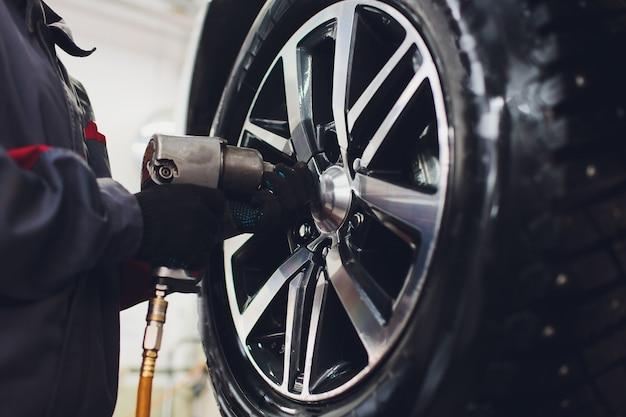Il riparatore equilibra la ruota e installa la gomma tubeless dell'auto sul bilanciatore nell'officina.
