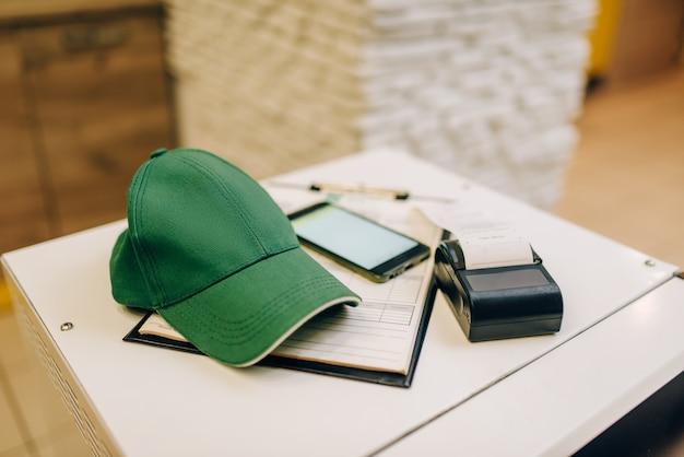 Il riparatore in uniforme tiene il telefono contro la cassetta degli attrezzi