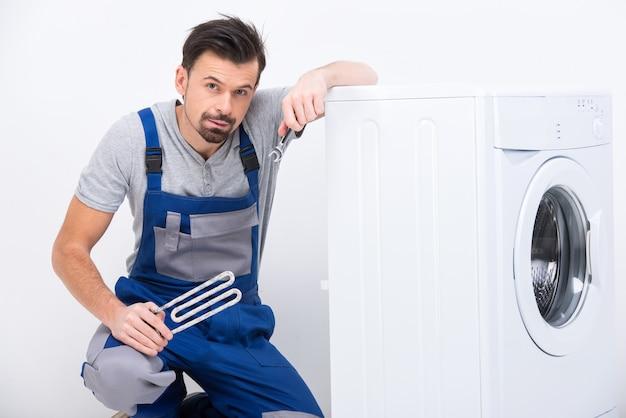 Il riparatore stanco sta riparando una lavatrice.