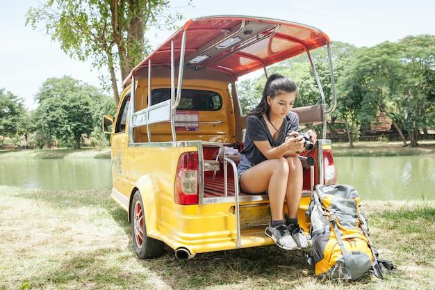 Il riposo asiatico della donna nel parco di ayutthaya di storia nazionale si siede sull'automobile di tuk tuk e guarda la sua macchina fotografica