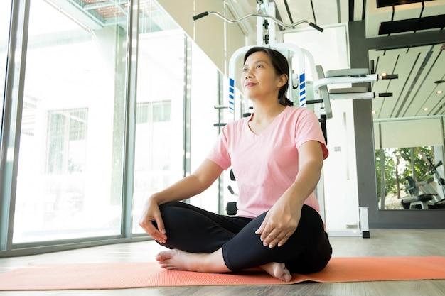 Il riscaldamento asiatico della donna di forma fisica prima di fa l'esercizio in palestra, yoga risolvente femminile di medio evo