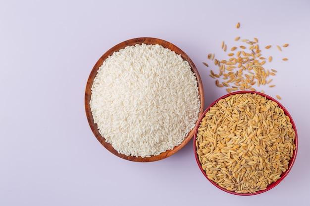 Il riso che è stato sbucciato è posto con la risaia su un bianco.