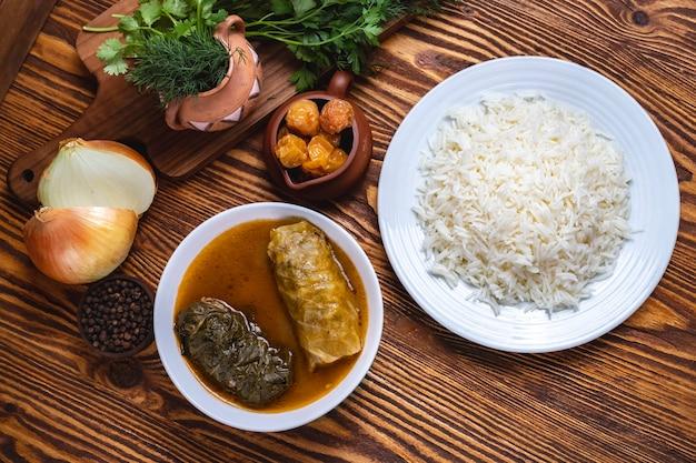 Il riso con il rotolo di cavolo inverdisce la vista superiore delle spezie della cipolla