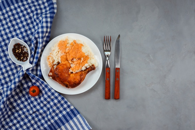 Il riso con salsa al curry con coscia di pollo fritto è servito sul piatto bianco. asciugamano blu, pepe nella ciotola a forma di pesce, coltello e forchetta decorano sfondo grigio.