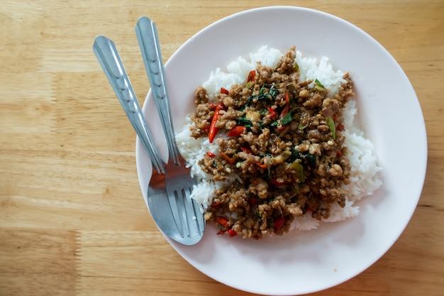Il riso ha completato con carne di maiale in padella e basilico in piatto bianco sulla tavola di legno.