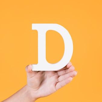Il ritaglio di carta della lettera d tiene a mano umana su sfondo giallo