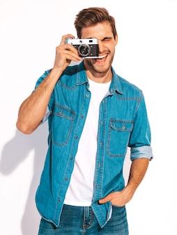 Il ritratto dei vestiti d'uso d'uso dei jeans dell'estate sorridente bello. maschera di presa maschio di modello sulla vecchia macchina fotografica d'annata della foto.