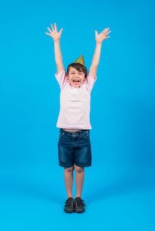 Il ritratto del cappello d'uso sorridente del partito del ragazzo con il braccio si è alzato in contesto blu