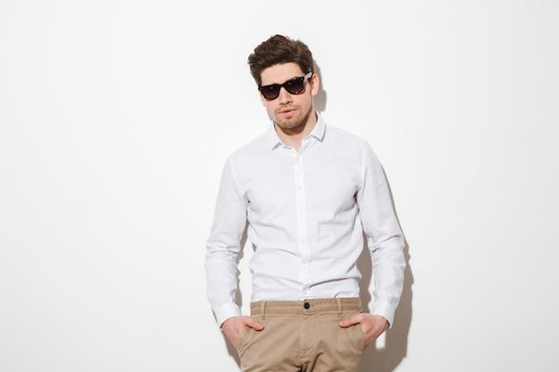 Il ritratto del giovane di modo si è vestito in camicia ed occhiali da sole che posano sulla macchina fotografica con le mani in tasche, sopra spazio bianco con ombra