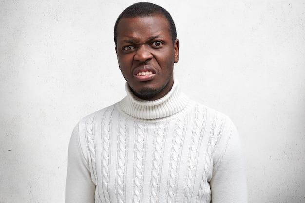 Il ritratto del giovane maschio afroamericano bello dispiaciuto ha un'espressione disgustosa, aggrotta le sopracciglia, esprime negatività, vestito con un maglione casual.
