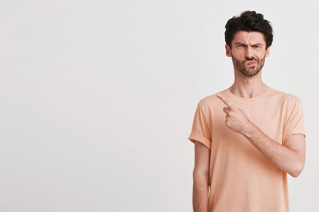 Il ritratto del giovane scontento infelice con setola indossa la maglietta della pesca sembra sconvolto e indica il lato con il dito isolato su bianco