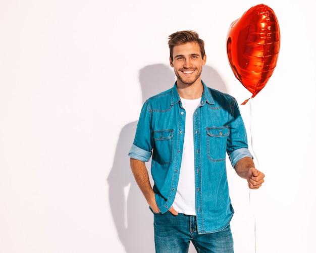 Il ritratto del modello alla moda sorridente bello dell'uomo si è vestito in vestiti dei jeans. pallone a forma di cuore della tenuta dell'uomo di modo.