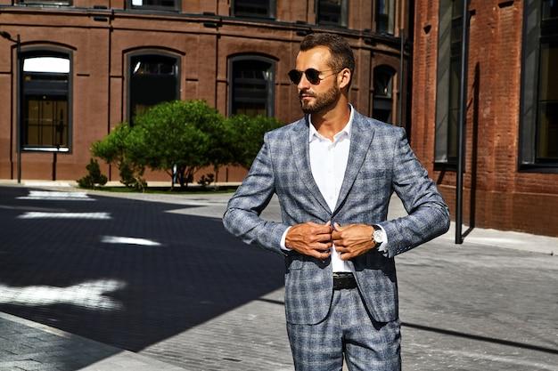 Il ritratto del modello bello sexy dell'uomo d'affari di modo si è vestito in vestito a quadretti elegante che posa sul fondo della via. metrosexual