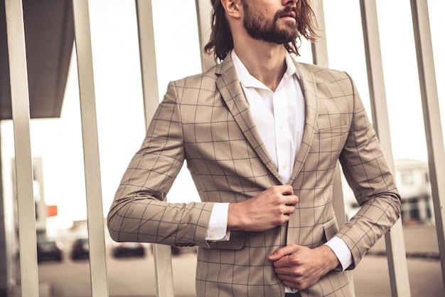 Il ritratto del modello bello sexy dell'uomo d'affari di modo si è vestito in vestito a quadretti elegante che posa vicino al muro di mattoni sui precedenti della via.