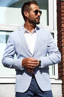 Il ritratto del modello bello sexy dell'uomo d'affari di modo si è vestito in vestito blu elegante che posa sul fondo della via. metrosexual