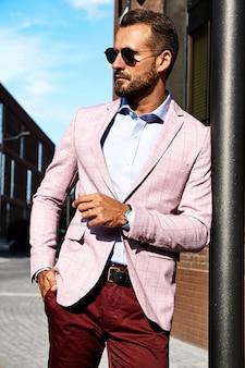 Il ritratto del modello bello sexy dell'uomo d'affari di modo si è vestito in vestito elegante che posa sul fondo della via. metrosexual