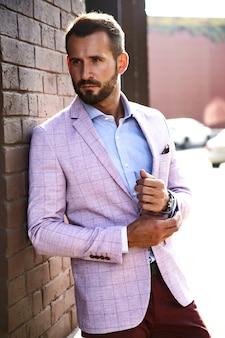 Il ritratto del modello bello sexy dell'uomo d'affari di modo si è vestito in vestito elegante che posa vicino al muro di mattoni sui precedenti della via. metrosexual