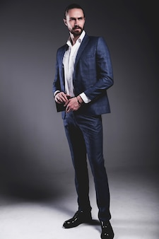 Il ritratto del modello dell'uomo d'affari alla moda dei pantaloni a vita bassa alla moda bello si è vestito in vestito blu elegante che posa sul gray