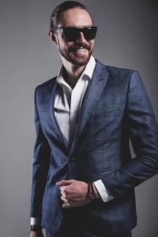 Il ritratto del modello dell'uomo d'affari alla moda dei pantaloni a vita bassa alla moda bello si è vestito in vestito blu elegante in occhiali da sole che posano sul gray