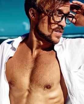 Il ritratto del modello di uomo prendente il sole bello che indossa la camicia bianca d'uso copre in vetri che posano sul cielo blu