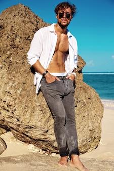 Il ritratto del modello di uomo prendente il sole bello che indossa la camicia bianca d'uso copre in vetri che posano vicino alle rocce sulla spiaggia dell'estate su cielo blu