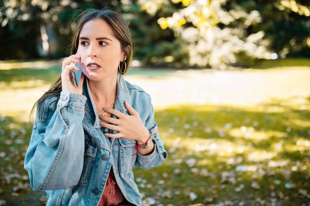 Il ritratto del primo piano del cellulare sollecitato della tenuta della donna preoccupato ha ricevuto le cattive notizie nel parco della città. emozione umana espressione faccia, sentimento, linguaggio del corpo di reazione. femmina con la mano aperta sul petto preoccupata.