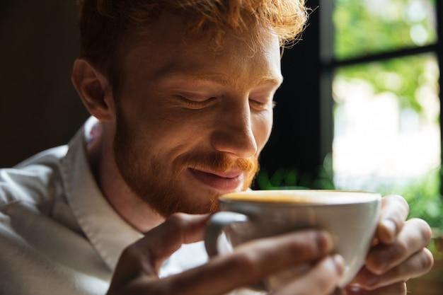 Il ritratto del primo piano dell'uomo barbuto della testarossa allegra annusa il caffè con gli occhi chiusi