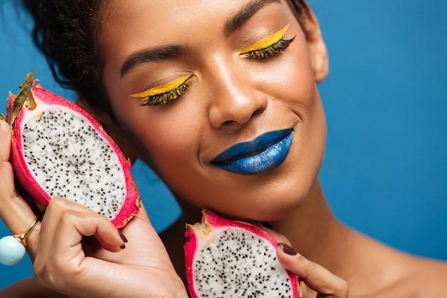 Il ritratto del primo piano della donna afro contenta con trucco luminoso che tiene la frutta di pitaya ha tagliato a metà prendendo piacere con gli occhi chiusi, sopra la parete blu