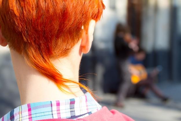 Il ritratto del primo piano di una ragazza dai capelli rossi con un taglio di capelli alla moda esamina un'esibizione dei musicisti di strada