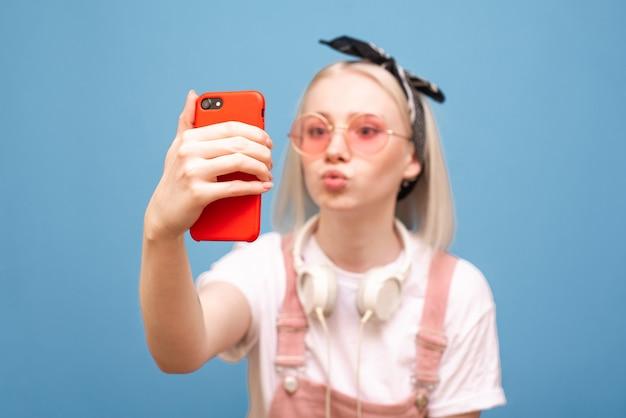 Il ritratto del primo piano di una ragazza divertente in vetri rosa luminosi prende un selfie su uno smartphone con una faccia divertente su un fondo blu