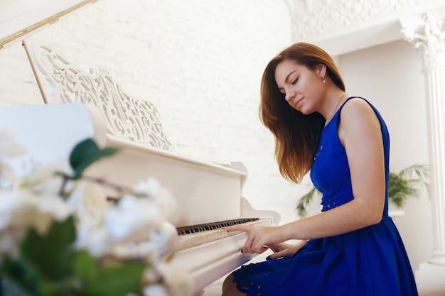 Il ritratto del primo piano di una ragazza in vestito blu che si siede al piano e gioca il piano
