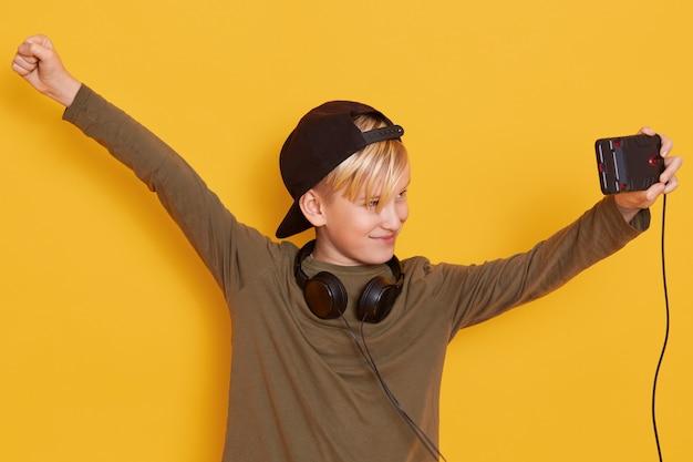 Il ritratto del ragazzino che tiene il suo cellulare moderno e che guarda il video, usando internet e le cuffie senza fili, si rallegra con le mani su