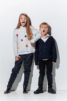Il ritratto del ragazzino e della ragazza svegli nella posa alla moda dei vestiti dei jeans