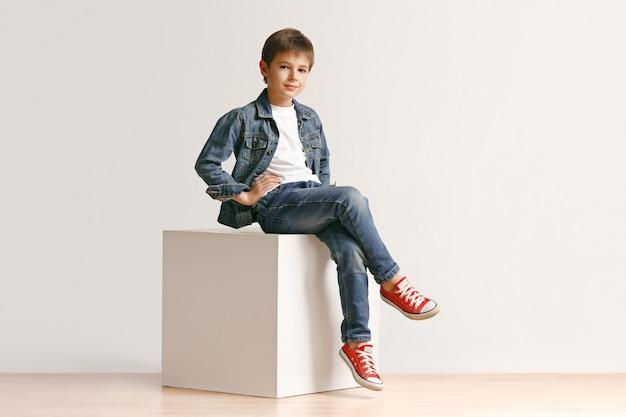 Il ritratto del ragazzino sveglio in vestiti di jeans alla moda che guarda l'obbiettivo contro il muro bianco dello studio. concetto di moda per bambini