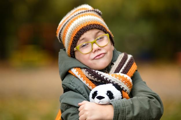 Il ritratto del ragazzo carino con gli occhiali e caldo cappello a maglia e sciarpa con il suo panda giocattolo nel parco in autunno