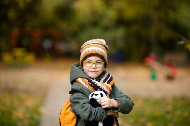 Il ritratto del ragazzo con gli occhiali e caldo cappello e sciarpa a maglia con il suo giocattolo nel parco in autunno