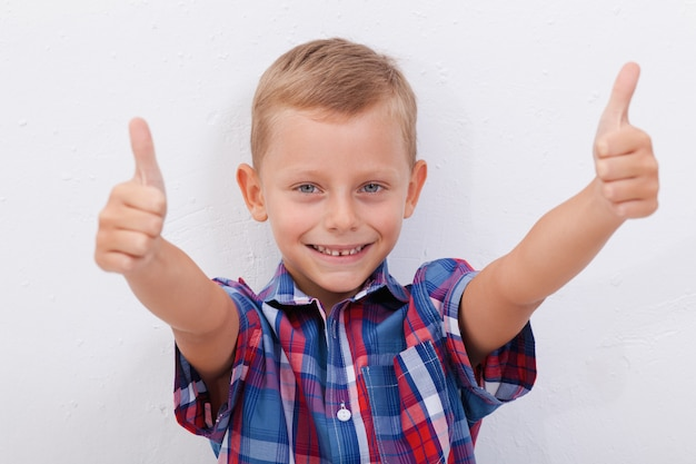 Il ritratto del ragazzo felice che mostra i pollici aumenta il gesto