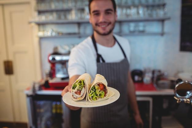 Il ritratto del servizio felice del cameriere rotola al self-service