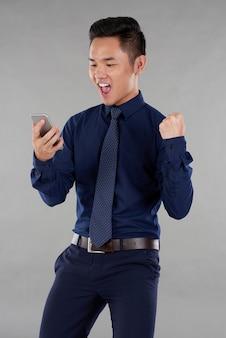 Il ritratto del tipo asiatico in vestiti astuti ha eccitato dalle notizie dello smartphone contro fondo grigio