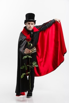 Il ritratto del vampiro caucasico bello che tiene rosso bello è aumentato sulla priorità bassa bianca dello studio.