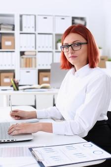Il ritratto dell'ufficio della testarossa della donna di affari si siede la tavola