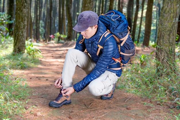 Il ritratto dell'uomo asiatico del viaggiatore che lega il laccetto prima esplora