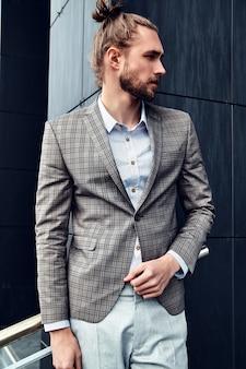 Il ritratto dell'uomo bello sexy si è vestito in vestito a quadretti beige elegante