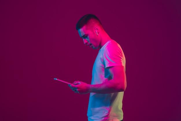 Il ritratto dell'uomo caucasico isolato alla luce al neon